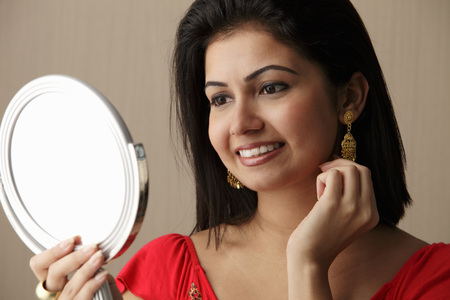 head shot of woman looking in the mirror and smiling