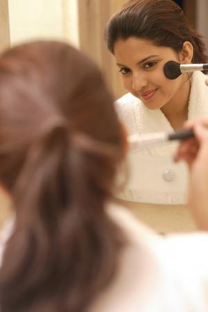 blusher: Woman applying blusher LANG_EVOIMAGES