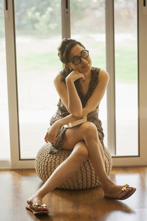 India, Woman wearing big glasses sitting on stool with head in hands