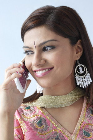 Young Indian woman on mobile phone LANG_EVOIMAGES