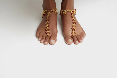 Womans feet with anklet against white floor