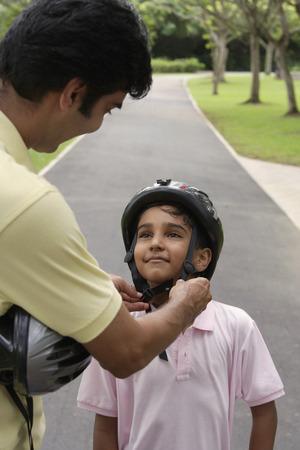 helpfulness: A father teaches his son to ride a bike