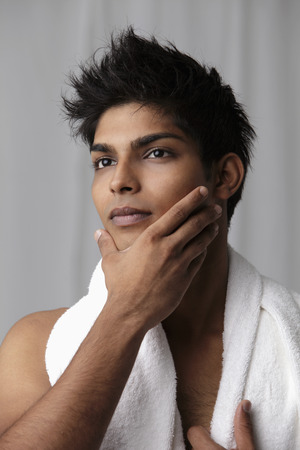 Young man feeling his chin with towel around his neck