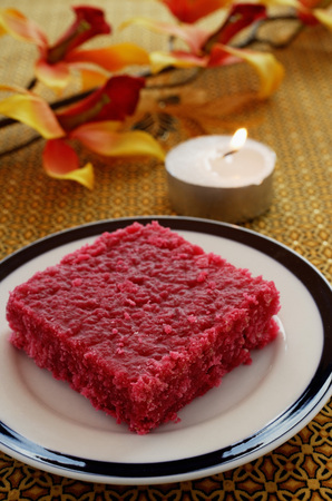 Red burfi with a candle