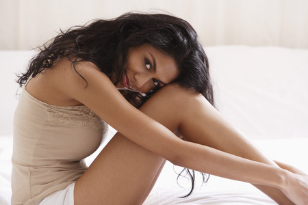 indian subcontinent ethnicity: Indian woman sitting on bed holding legs