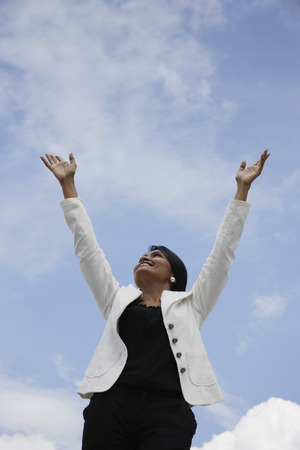 Indian woman looking up with arms reaching to the sky