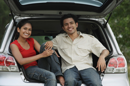 Young couple sitting in car boot smiling at camera