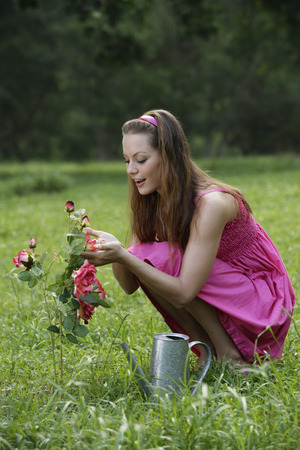 Young woman tending to flowers LANG_EVOIMAGES