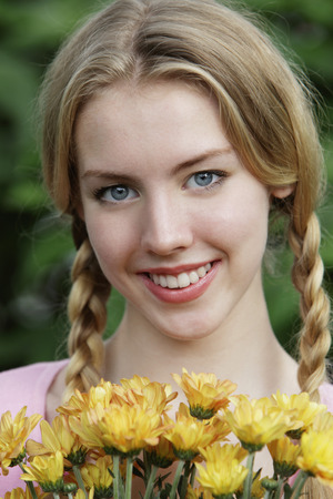 Head shot of young woman holding flowers Stock Photo