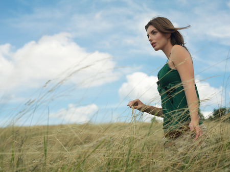 Young woman walking in grassy field