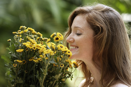 Young woman smelling big bunch of daisies