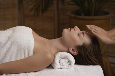 reiki: Young woman receiving reiki massage LANG_EVOIMAGES