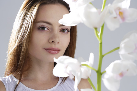 Young woman peering through orchid branch