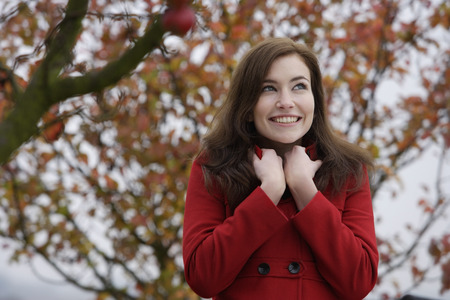young woman in red coat under apple tree