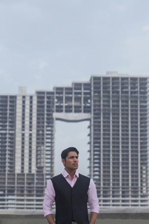 India, Man wearing waistcoat standing with hands in pockets outside building under construction Stock Photo