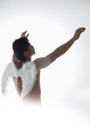 Man wearing angel wings, holding arms upward