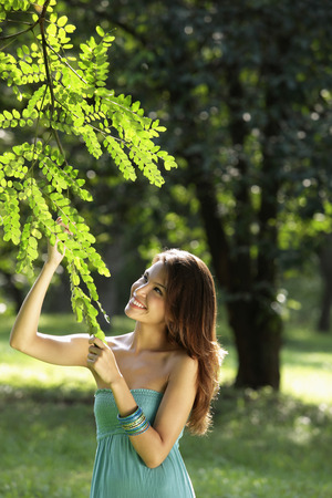young woman looking at leaves of tree and smiling LANG_EVOIMAGES