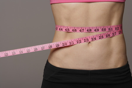torso of woman measuring her waist Stock Photo