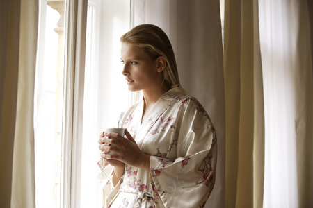 think through: Young woman standing with coffee cup by window LANG_EVOIMAGES
