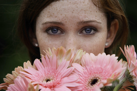 high section: Close up of young woman smelling daisies