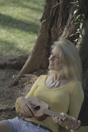 under a tree: Young woman playing ukulele under a tree