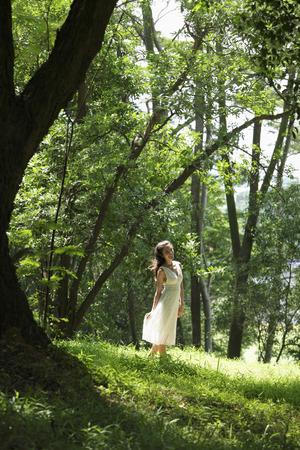 young woman wearing white dress walking among trees Stock Photo