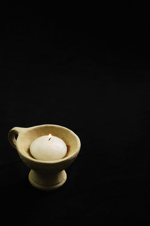 손으로 점토 냄비에 흰색 촛불