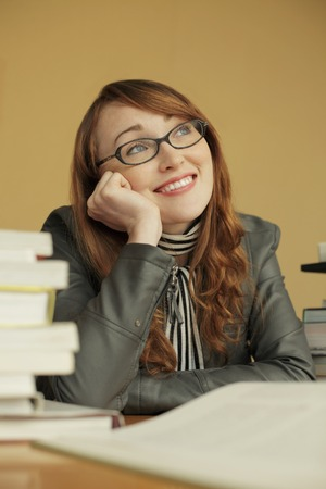 Young woman looking up and smiling while studying Stock Photo