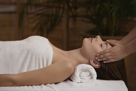 head profile: Young woman receiving reiki massage LANG_EVOIMAGES