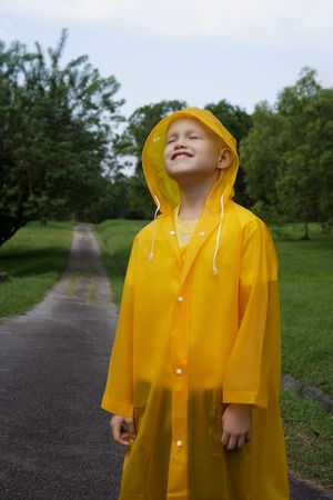 young boy standing on road in rain coat