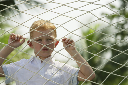 boy looking through net