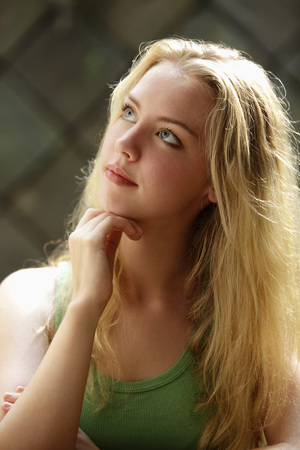 Portrait of young woman with long blonde hair looking up