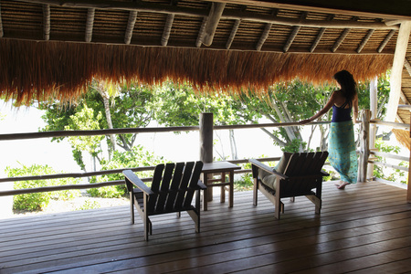 back view of woman looking over a balcony with thatched roof Stock Photo