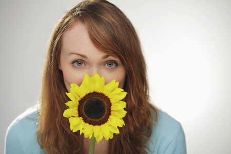 Red haired woman with sunflower in front of her face LANG_EVOIMAGES