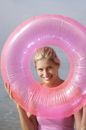 woman at beach with pink tube LANG_EVOIMAGES