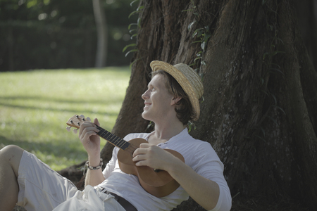 under a tree: Young man playing ukulele under a tree
