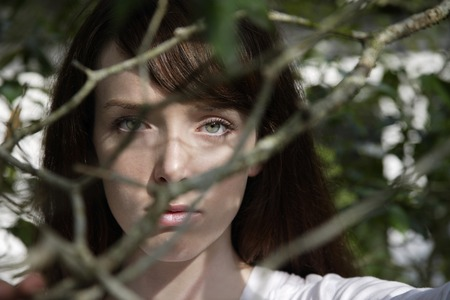 young woman looking through branches Stock Photo