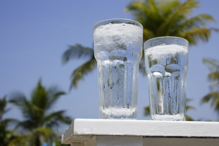 two glasses of ice water on white table