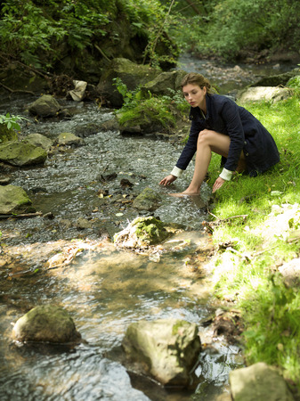 ankle deep in water: Young woman putting hand in stream