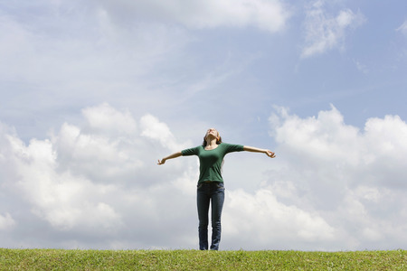 Teen girl standing on grass, arms spread LANG_EVOIMAGES