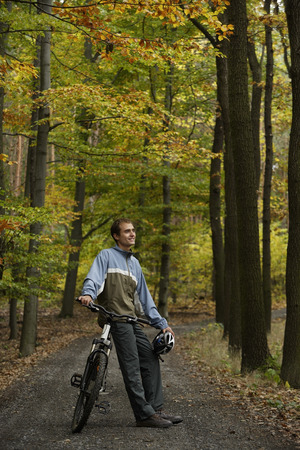 Young man taking rest from bike ride through forest