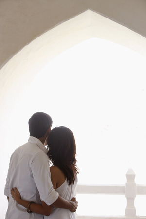 back view of couple wearing all white, embracing Stock Photo
