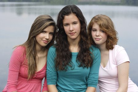 湖の横の壁に座っている十代の若者たちのグループ