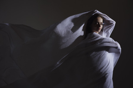 Young woman wrapped in white fabric