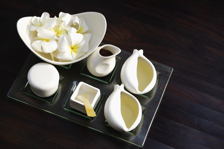 Set of white vessels on tray, Frangipani flowers in bowl