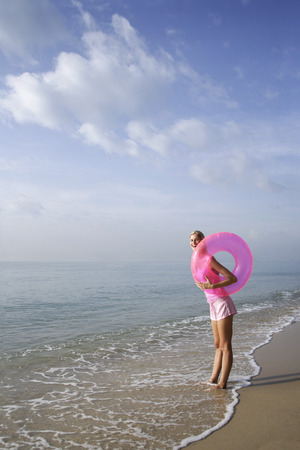 ankle deep in water: woman at beach with pink tube LANG_EVOIMAGES