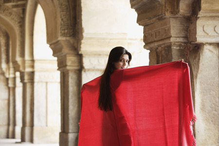 Woman in red shawl, standing in ancient monument