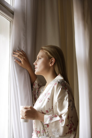 Young woman standing at window with coffee cup Banco de Imagens