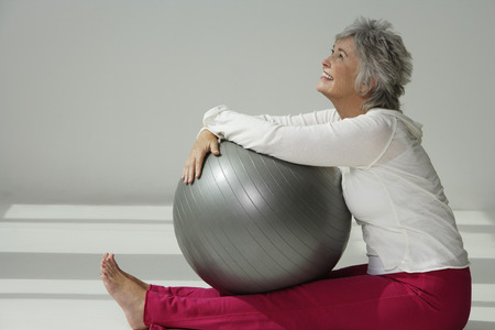 the well groomed: Mature woman holding exercise ball, looking up.