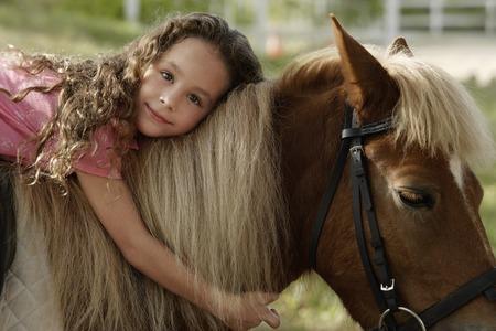 Young girl hugging pony